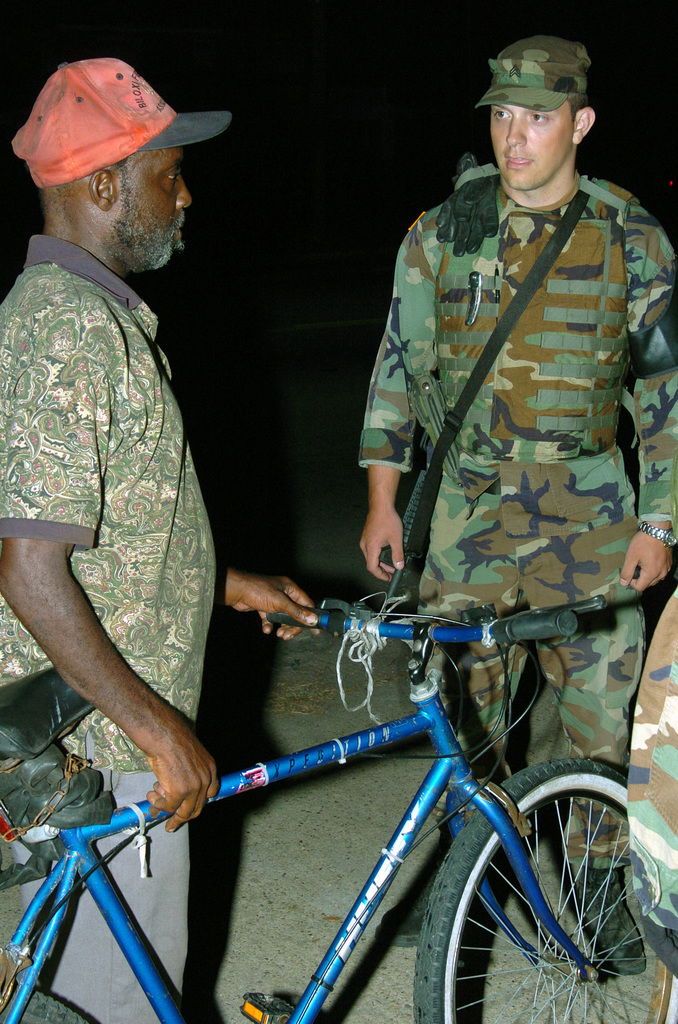 Michigan Army National Guard (MIARNG) Sergeant (SGT) Matt Bartholomew, with the Taylor, Michigan (MI), 1776th Military Police Company (MPC), speaks to a Gulfport, Mississippi (MS), resident during a night patrol. The 1776th MPC is deployed to Mississippi to augment local law enforcement agencies and provide humanitarian assistance in support of Operation KATRINA RELIEF. (A3596)
