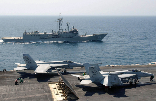 """With the Royal Australian Navy (RAN) Adelaide (Oliver Hazard Perry) Class: Frigate, Her Majestys Australian Ship (HMAS) NEWCASTLE (FFG 06) underway in the background, two US Navy (USN) F/A-18E Super Hornet aircraft, assigned to the """"Tophatters"""" of Strike Fighter Squadron Fourteen (VFA-14), prepare to launch from the flight deck of the USN Aircraft Carrier, USS NIMITZ (CVN 68). The Nimitz Carrier Strike Group is currently on a regularly scheduled deployment participating in Maritime Security Operations (MSO) in the Persian Gulf area"""
