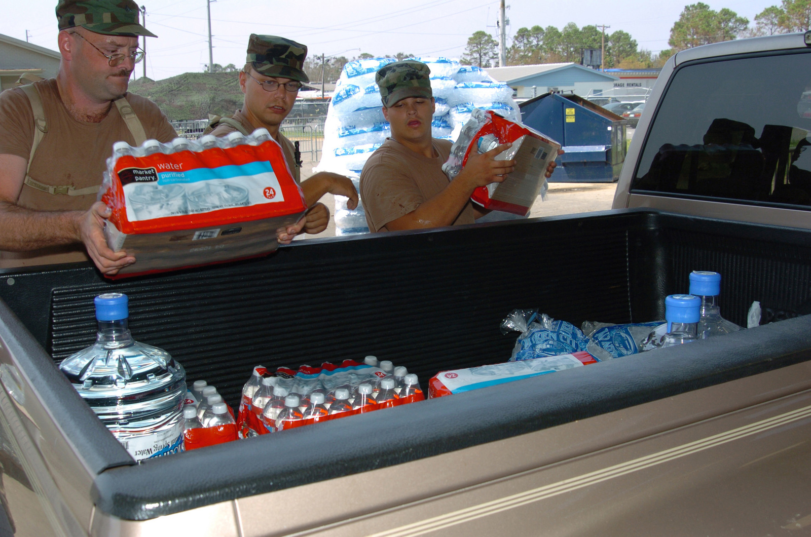 Michigan Army National Guard (MIARNG) (left to right), Sergeant (SGT) David Moore, SPECIALIST (SPC) Joshua Rushlow and Private First Class (PFC) Brent Halfma, with the Taylor, Michigan (MI), 1776th Military Police Company (MPC), assist with water and ice distribution at the Pascagoula Fairgrounds, Mississippi (MS). The 1776th MPC is deployed to Mississippi to augment local law enforcement agencies and provide humanitarian assistance in support of Operation KATRINA RELIEF. (A3596)