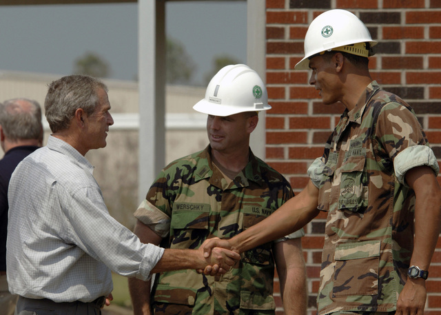 US President George W. Bush conveys his gratitude to US Navy (USN) Lieutenant Junior Grade (LTJG) Sam Werschky (center) and CHIEF Builder (BUC) Dan Walker, for the excellent work the Seabees of Naval Mobile Construction Battalion One (NMCB-1), are accomplishing during the clean-up efforts underway at the 28th Street Elementary School in Gulfport, Mississippi (MS). President Bush is currently visiting the Gulf Coast region to assess the damage and disaster recovery efforts from Hurricane Katrina. The USN is currently involved in Hurricane Katrina humanitarian assistance operations, led by the Federal Emergency Management Agency (FEMA), in conjunction with the Department of Defense (DOD)