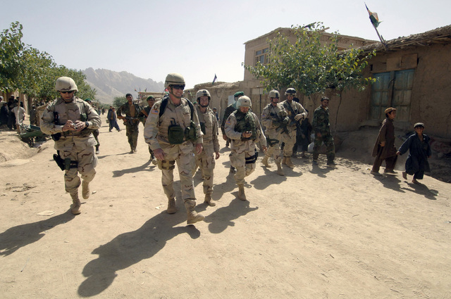 Afghan locals and American Soldiers in body gear, armed with M4/M4A1 5.56 mm Carbine rifles, guard (left to right) US Army (USA) Colonel (COL) Paul Calbos Major (MAJ) Joseph Kuchan, Captain (CPT) Scott Handler and COL James Coffman as they walk throughout Camp Kackeran, in support of Operation ENDURING FREEDOM