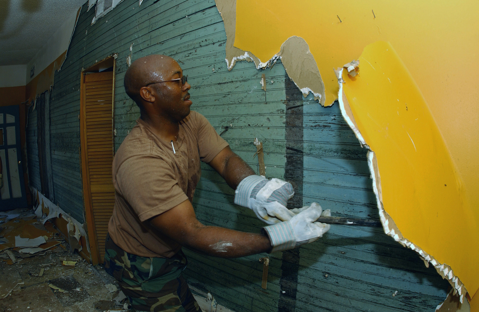 Mississippi Air National Guard (MSANG) MASTER Sergeant (MSGT) Felix Gines, 209th Combat Regional Training Center, removes plasterboard from a Hurricane Katrina flood damaged home in D'Iberville, Mississippi (MS). The plasterboard must be removed because of mold that grew on it after it is submerged in the floodwaters from the storm surge