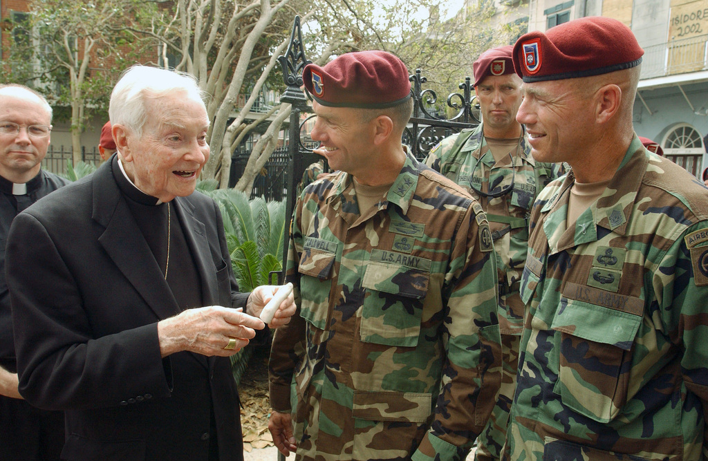 The Archbishop of the state of Louisiana (LA), Phillip Hannan, thanks US Army (USA) Major General (MGEN) William Caldwell, IV (center), Commander of the 82nd Airborne Division (AD) and Command Sergeant Major (CSM) Wolf Amacker, during a visit to the St. Louis Cathedral, in New Orleans. The USA had found and returned a missing finger broken off a Jesus statue damaged by Hurricane Katrina