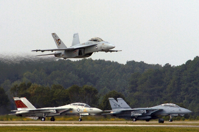 A US Navy (USN) F/A-18F Super Hornet, Strike Fighter Squadron 106 (VFA-106), Gladiators, Naval Air Station (NAS) Oceana, Virginia (VA), flies low past two F-14 Tomcats, Fighter Squadron 101 (VF-101), Grim Reapers (left), and Fighter Squadron 32 (VF-32), Swordsman, also from NAS Oceana, waiting on the runway during the 2005 NAS Oceana Air Show. The air show showcased civilian and military aircraft from the Nation's armed forces, providing many flight demonstrations and static displays