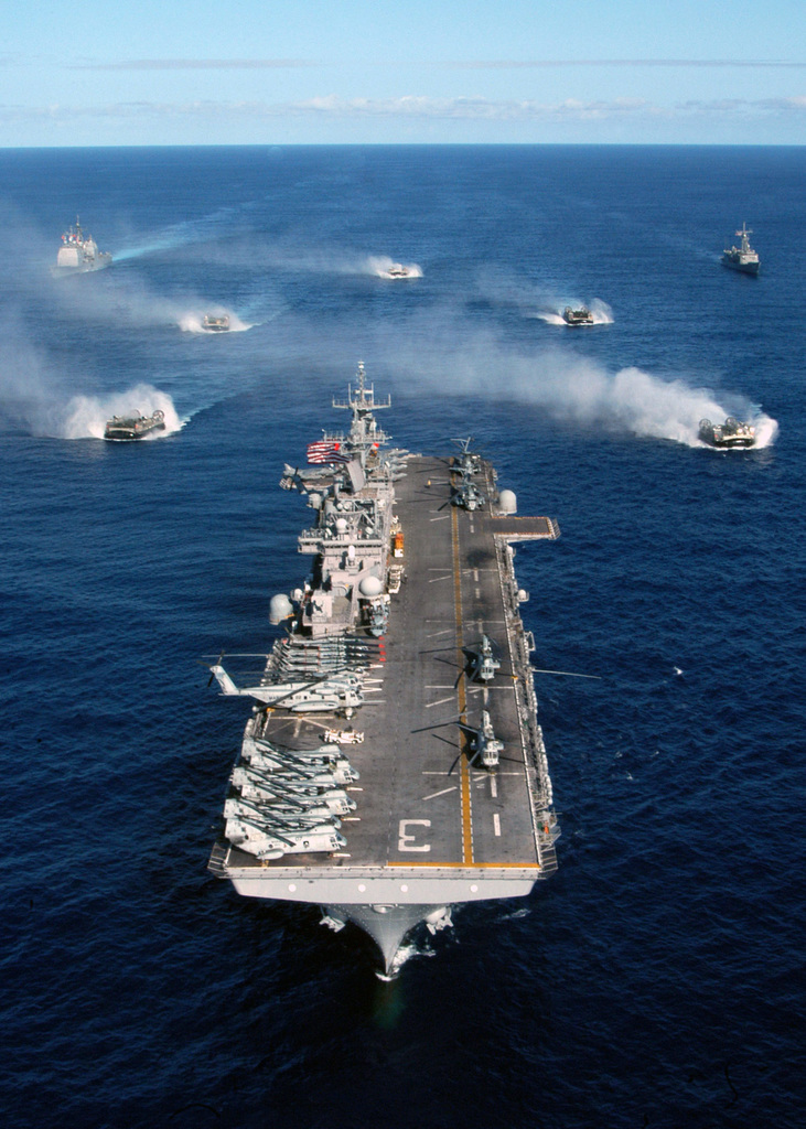 The US Navy (USN) Wasp Class Amphibious Assault Ship USS KEARSARGE (LHD 3) leads the formation followed by Landing Craft, Air Cushions (LCAC) assigned to Assault Craft Unit-4 (ACU-4). They are flanked by USN Ticonderoga Class Guided Missile Cruiser USS NORMANDY (CG 60) (left) and USN Oliver Hazard Perry Class Frigate USS KAUFFMAN (FFG 59). The Kearsarge Expeditionary Strike Group (ESG), on the Atlantic Ocean, is returning to homeport Naval Station (NS) Norfolk, Virginia (VA), after a regularly scheduled deployment in support of the Global War on Terrorism (GWOT)