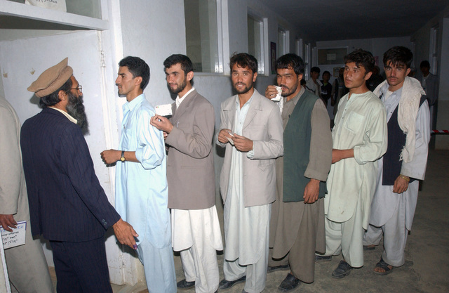 Afghans wait in line at a polling station in the Parwan Province to vote in the country's first parliamentary elections, during Operation ENDURING FREEDOM