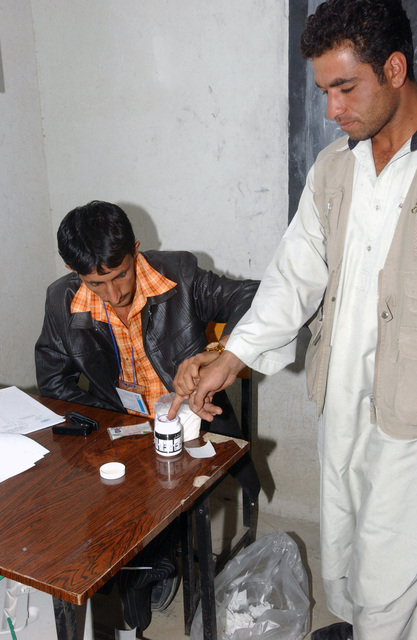 An Afghan citizen dips his finger in ink. The ink stained finger shows he has voted in the country's first parliamentary elections, during Operation ENDURING FREEDOM