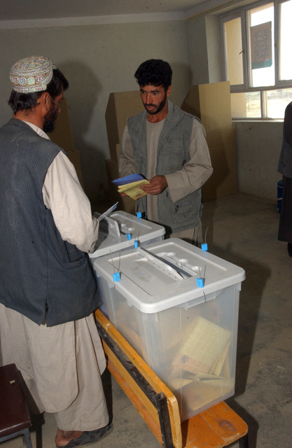 An Afghan citizen is instructed were to place his ballot after voting in the countries first parliamentary elections, Sept 18, 2005. (U.S. Army photo by SPC. Jason R. Krawczyk) (Released)