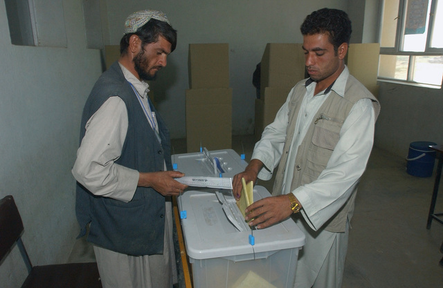 An Afghan citizen places his ballot in a box after he voted in the countries first parliamentary elections, during Operation ENDURING FREEDOM