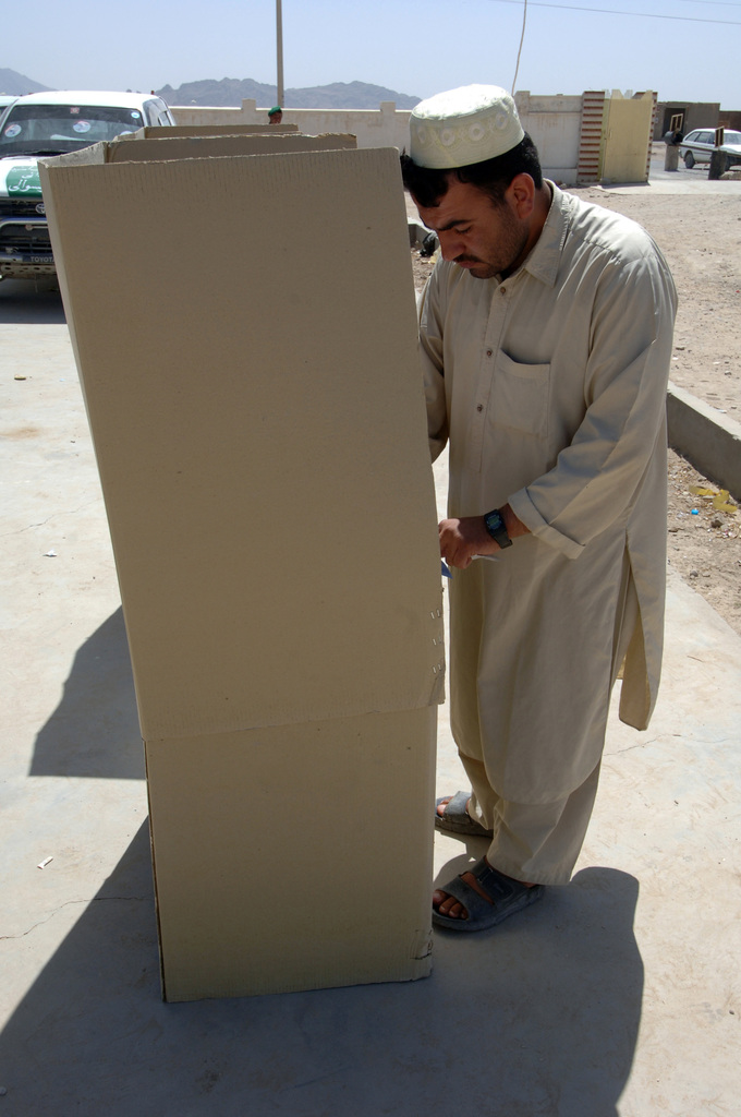 An Afghan man is behind a cardboard booth voting for candidates in the Zhari district, Kandahar Province on Sept. 18, 2005.  The Afghan people went to the voting polls to vote for parliament and provincial candidates. The Afghan people want to put new candidates in office who would make a difference in their district. (U.S. Army photo by SGT. ANDRE Reynolds) (Released)
