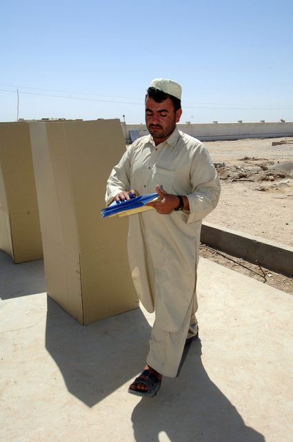 An Afghan man leaves a cardboard booth with both of his ballots in his hand to place them in the ballot boxes at the districrt headquarters of the police chief in Zhari district, Kandahar Province on Sept. 18, 2005.  The Afghan people went to the voting polls to vote for parliament and provincial candidates. The Afghan people want to put new candidates in office who would make a difference in their district. (U.S. Army photo by SGT. ANDRE Reynolds) (Released)