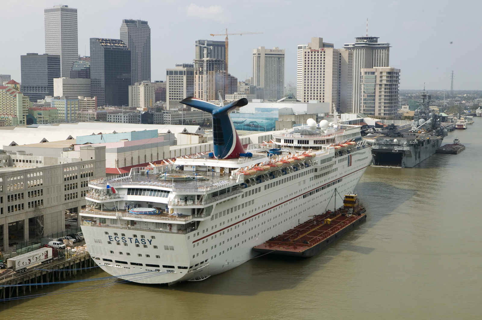 [Hurricane Katrina] New Orleans, LA., 9/18/2005 -- Cruise ship Ecstasy docked with the city of New Orleans in the background. Thousands of Hurricane Katrina survivors and response workers stayed on the Ecstasy due to the lack of housing in and around New Orleans.  FEMA photo/Andrea Booher