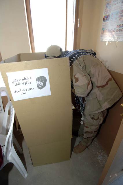 Mr. Abdullah Qarani, an interperter for the U.S. Forces, Is at his booth choosing his candidates to vote for, he has two ballots to chose from, parliament ballot (blue one) and a provincial ballot (yellow one) of the candidates in the Zhari district on Sept. 18, 2005. The Afghan people went to the voting polls to vote for parliament and provincial candidates in the Zhari district, Kandahar Province. (U.S. Army photo by SGT. ANDRE Reynolds) (Released)