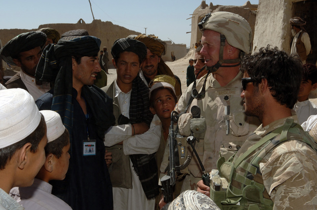 U.S. Army LT. COL. Timothy McGuire, from 1ST Battalion, 508th Infantry, and his interpreter, right, speak with a recent Afghan National Army graduate, left, during a visit in Seghana, Afghanistan, Sept. 18, 2005.  The visit in Seghana is conducted as a part of security patrol on the day of parliamentary elections in Afghanistan.  (U.S Army photo by PFC. Michael Zuk)  (Released)