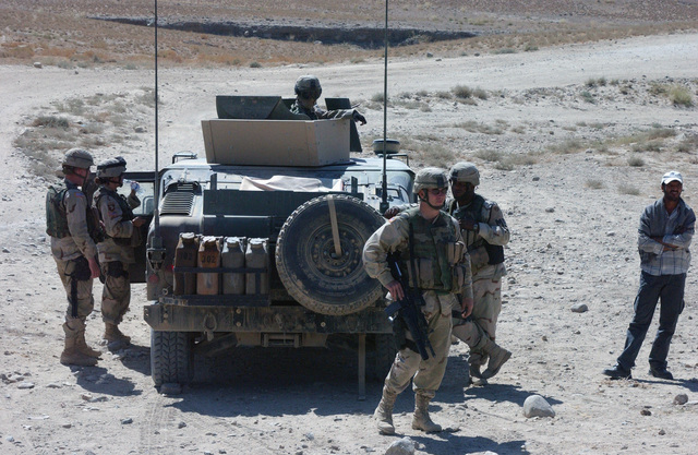 US Army (USA) Military Police (MP) from the 164th MP Company, Fort Richardson, Alaska (AK), set up a listening and observation post while on patrol during the Afghan Parliamentary Elections, in support of Operation ENDURING FREEDOM. An M998 High-Mobility Multipurpose Wheeled Vehicle (HMMWV) is in the background