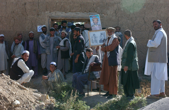 Voters in the Habdullma Lek Village hold signs while waiting in line to vote during Afghanistan's first parliamentary elections and during Operation ENDURING FREEDOM
