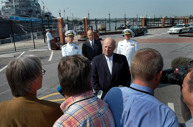 His Majesty King Harald V (center), King Norway, answers reporters questions at the conclusion the re-enactment the 1942 ceremony when the United States transferred the US Navy (USN) PC-461 Patrol Craft Class Submarine Chaser USS PC-467 to the Royal Norwegian Navy, later renamed the KING HAAKON (P390), while (left to right) USN Admiral Michael G. Mullen, CHIEF Naval Operations (CNO); the Honorable Dionel M. Aviles, Under Secretary the Navy (USECNAV); and USN Rear Admiral (RDML) Jan C. Guadio, 84th Commandant Naval District Washington (NDW); are seen standing in the background. His Majesty King Harald V is on an ficial visit to the United States celebrating 100 years...