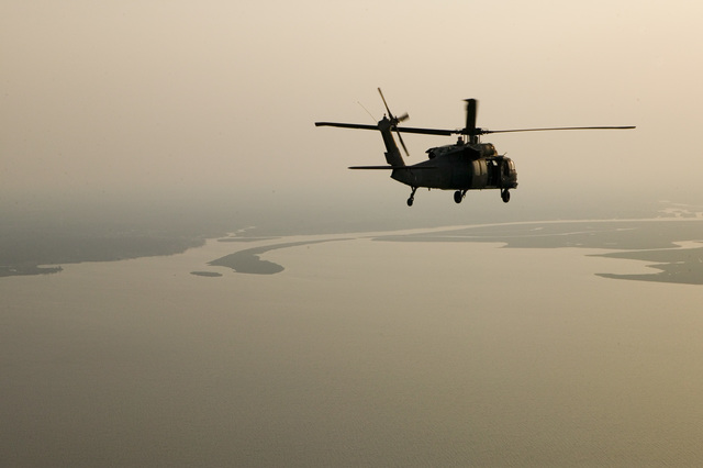 [Hurricane Katrina] New Orleans, LA., 9/19/2005 -- An Air Force helicopter flys over Lake Ponchatrain to New Orleans after a Congressional aerial tour of damages in Mississippi and Louisianna following Hurricane Katrina.  Andrea Booher/FEMA