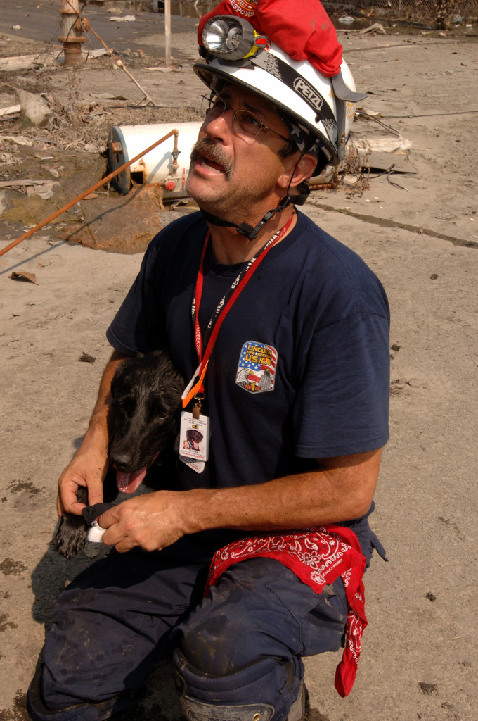 [Hurricane Katrina] New Orleans, LA, September 19, 2005 -- A FEMA Urban Search and Rescue worker looks after his rescue dog who injured his paw while searching in a neighborhood affected by Hurricane Katrina.  Jocelyn Augustino/FEMA