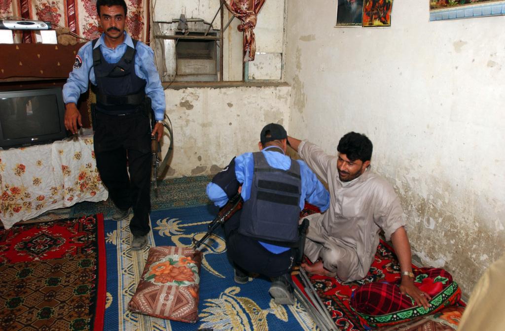 Iraqi police search the inside of a house in Al Madain, Iraq