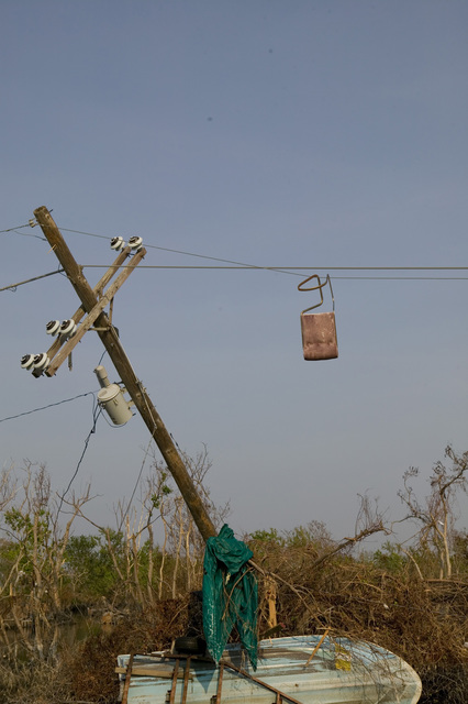 [Hurricane Katrina] Plaquemines Parish, LA., 9/21/2005 -- A chair hangs from a telephone line and a boat is smashed into a telephone pole - signs of the destruction in the fishing community of Plaquemines Parish following Hurricane Katrina.  FEMA photo/Andrea Booher