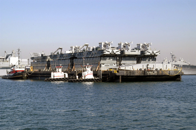 The US Navys (USN) Improved Modular Lighterage System (INLS) ramp module loaded on a barge for transit from New Orleans, Louisiana (LA), to Coronado (CO), California (CA) for testing by Expeditionary Warfare Training Group Pacific (EWTGPAC) and Amphibious Construction Battalion One (ACB-1). The INLS is a redesign of a floating dock system originally used during World War II (WWII). The system assembles to form ferries, causeway piers, or ships ramp roll-off discharge platforms, providing the Navy and US Marine Corps (USMC) with a safer, more versatile way to deliver vehicles and critical supplies from ship to shore during war or peacetime operations