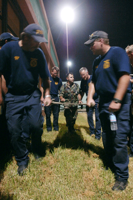 US Air Force (USAF) Technical Sergeant (TSGT) Carlos Israel Estrada instructs firemen from Beaumont and Port Arthur, Texas (TX), in the setup and use of a litter. Local emergency officials worked with Airmen from the 433rd Aeromedical Evacuation Squadron (AES), Lackland Air Force Base (AFB), Texas (TX), and the 183rd AES, Mississippi Air National Guard (MSANG), to evacuate people before the arrival of Hurricane Rita