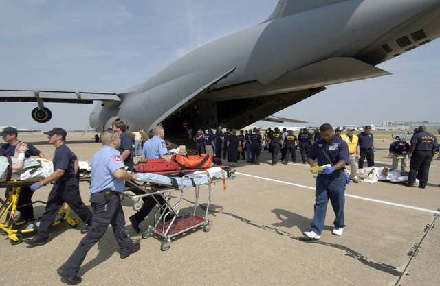 Hospital patients from Beaumont, Texas (TX), are taken off a US Air Force (USAF) C-5 Galaxy cargo aircraft from the 21st Airlift Squadron (AS), Travis Air Force Base (AFB), California (CA), en route to one of many medical facilities set up to care for Hurricane Rita evacuees
