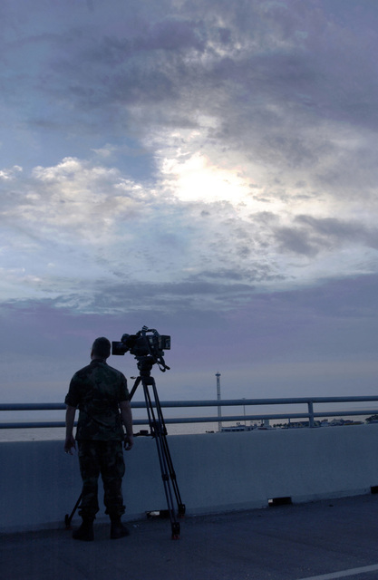 Tennessee Air National Guard (TNANG) MASTER Sergeant (MSGT) Buck Kahler, Training and Education Centers Multimedia Branch (TEC/TV), Det 10, McGhee-Tyson Air National Guard Base (ANGB), Tennessee (TN), watches the sun rise as he waits to captures Hurricane Rita approaching the Texas (TX) coast at Galveston Bay
