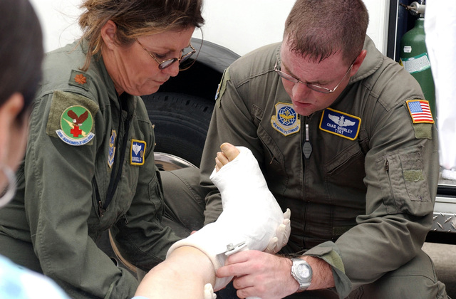 US Air Force (USAF) Major (MAJ) Susan Martello (left) and USAF Technical Sergeant (TSGT) Chad Ghorely, both Aeromedical Technicians assigned to the 156th Aeromedical Evacuation Squadron (AES), North Carolina Air National Guard (NCANG) remove a new cast off a patient's leg before the patient is loaded onto a USAF C-130 Hercules aircraft at Sebring Airport, in Florida (FL), in preparation from a flight back to Key West, during Hurricane Rita humanitarian assistance operations, Joint Task Force (JTF) Rita