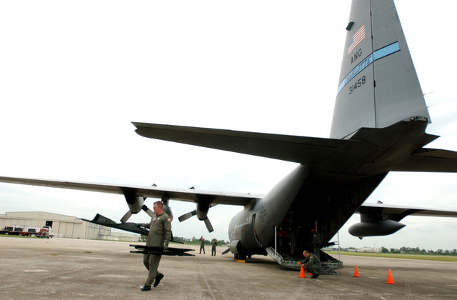 US Air Force (USAF) Technical Sergeant (TSGT) Chad Ghorley (foreground), Aeromedical Technician, 156th Aeromedical Evacuation Squadron (AES), North Carolina Air National Guard (NCANG) helps to offload cots for a USAF C-130 Hercules aircraft at Sebring Airport, in Florida (FL), following a mission to fly elderly Hurricane Rita evacuees back to Key West, during Hurricane Rita humanitarian assistance operations, Joint Task Force (JTF) Rita