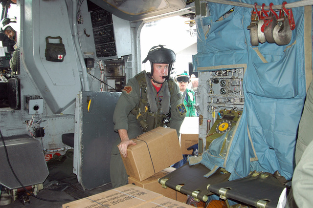 US Navy (USN) Pilots assigned to Helicopter Mine Countermeasure Squadron 14 (HM-14), Naval Air Station (NAS) Norfolk, Virginia (VA), unload meals, ready to eat (MRE) for survivors of Hurricane Rita gathered in a Mississippi field. The Navy is contributing to the humanitarian assistance operations led by the Federal Emergency Management Agency (FEMA) in conjunction with the Department of Defense (DoD)