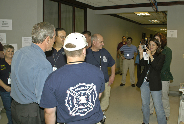 [Hurricane Katrina] Baton Rouge, LA, 9-25-05 -- President George W Bush takes time for a photo with FEMA Workers at the Joint Field Office.  President Bush was in the area to gather first hand information from Admiral Thad Allen (background) about the recovery efforts of Hurricane Katrina and damage from Hurricane Rita.  MARVIN NAUMAN/FEMA photo