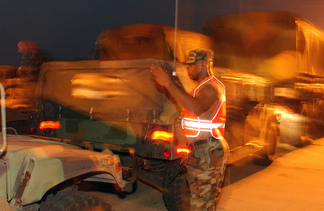 US Army (USA) SPECIALIST Fourth Class (SPC) Joseph Thorne, 3rd Battalion (BN), 112th Field Artillery (FA), New Jersey Army National Guard (NJARNG), Morristown, New Jersey (NJ), guides vehicles into position as they arrive at the intermediate staging base near Alexandria, Louisiana (LA). More than 2,000 vehicles and 4,000 troops were assembled at the central Louisiana location waiting to receive orders for recovery missions along Louisiana's Gulf coast following Hurricane Rita. (Duplicate image, see also DFSD0602372 or search 050925F4970D103)