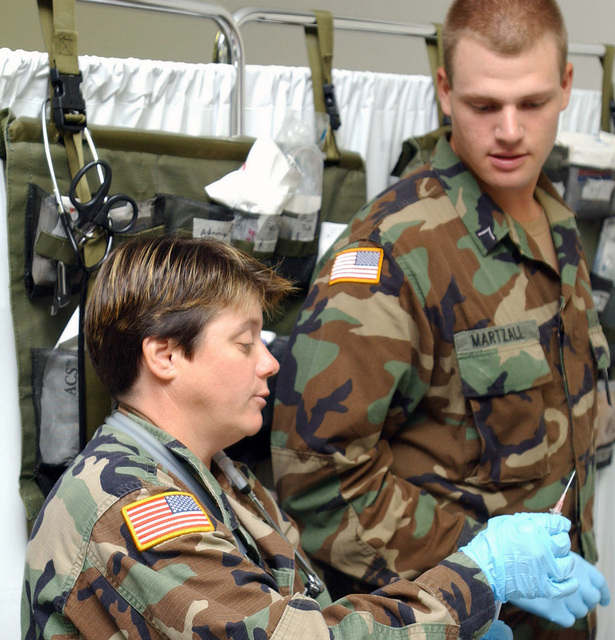 US Army (USA) Sergeant (SGT) Debra Markland (foreground), assigned to C Company, 328th Medical Battalion, instructs USA Private (PVT) Corey Martzall on how to properly administer an inoculation at the Troop Medical Clinic located at England Air Force Base (AFB), Louisiana (LA). (A3530)