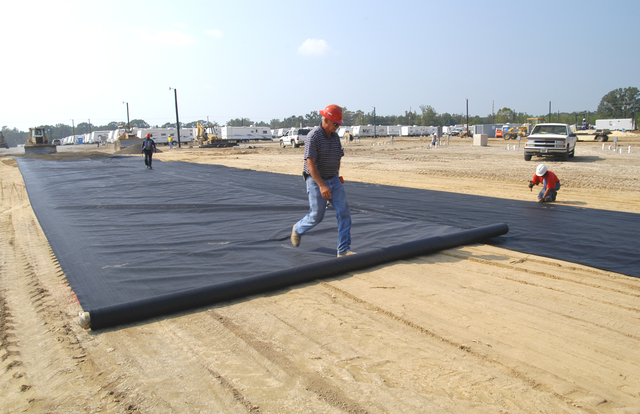 [Hurricane Katrina] Baker, LA, September 29, 2005 -- As a crew chief rolls out a rock/soil protective barrier before a gravel base is put into place, other crew members smooth it out and secure the edges to bind it to the ground. This FEMA temporary housing site is one of several planned for this area to provide living quarters for individuals and families left homeless by Hurricane Katrina.  Win Henderson / FEMA