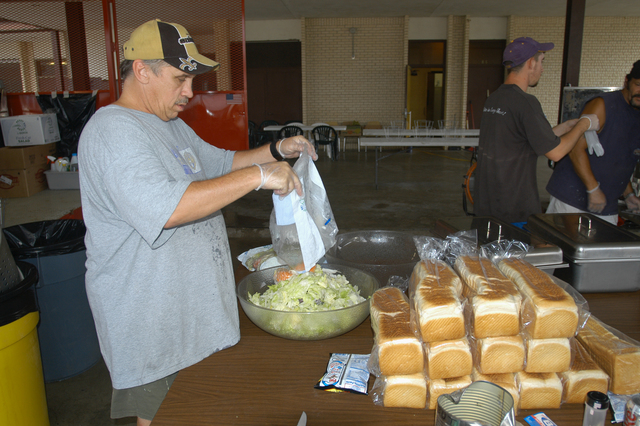 [Hurricane Rita] Iowa, LA, September 30, 2005 -- A catering crew hired to feed the soldiers from a Monroe, LA National Guard unit prepare the evening meal by making the salad and cooking the meats to be served. The guardsmen are providing ice, water and Meals Ready to Eat to area residents left without electrical power by Hurricane Rita.  Win Henderson / FEMA