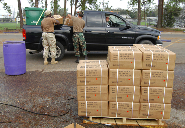 [Hurricane Rita] Iowa, LA, September 30, 2005 -- National guardsmen from Monroe, LA provide the manpower to load Meals Ready to Eat into the back of a pickup truck at a distribution center set up to provide water, ice and food to area residents left without power by Hurricane Rita.  Distribution centers throughout the state are giving essential commodities to thousands of people daily.  win Henderson / FEMA