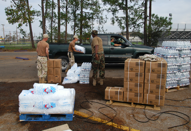 [Hurricane Rita] Iowa, LA, September 30, 2005 -- National Guardsmen from Monroe, LA empty pallets of Meals Ready to Eat, water and ice as they place these valuable commodities into the trunks of cars and backs of pickup trucks driven by local residents.  Thousands of people in this area of the state were left without power by Hurricane Rita.  Win Henderson / FEMA