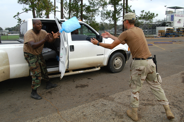 [Hurricane Rita] Iowa, LA, September 30, 2005 -- Two soldiers, part of a National Guard unit from Monroe, LA, stock the rear area of a pickup truck with bags of ice.  The loss of electric power in this area, caused by Hurricane Rita, makes ice a valuable commodity for area residents.  Win Henderson / FEMA