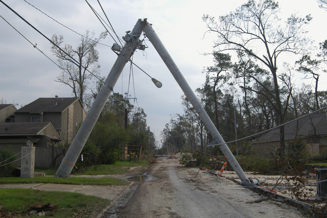 """[Hurricane Rita] Lake Charles, LA, September 30, 2005 -- A metal power pole, snapped in the middle, forms an inverted """"V"""" over a neighborhood road.  Hurricane Rita left thousands of residents in southwestern Louisiana without power.  Win Henderson / FEMA"""