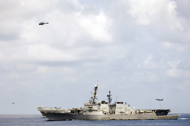 The US Navy (USN) Arleigh Burke Class Guided Missile Destroyer USS HIGGINS (DDG 76) (foreground) and the Indian Hermes Class Aircraft Carrier INS (Indian Navy Ship) VIRAAT (R 22) underway in the Indian Ocean as part of Exercise MALABAR 2005. The exercise is designed to increase interoperability between the two navies while enhancing the cooperative security relationship between India and the United States. The at-sea exercise includes maritime interdiction, surface events, sub-surface, air events, and personnel exchanges. Indian aircraft in the image include a Chetak helicopter (top), Sea King helicopter (left) and a Sea Harrier lifting off the rear of the VIRAAT