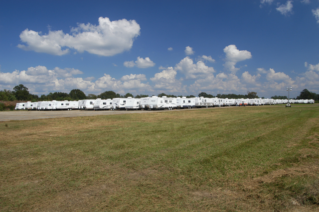 [Hurricane Katrina/Hurricane Rita] Baton Rouge, LA, October 1, 2005 -- A solid white line, made up of hundreds of travel trailers waiting for deployment to private and public sites, marks the separation between earth and sky at a staging area here.  Thousands of travel trailers and mobile homes will be set in place throughout the state to provide temporary housing for residents left homeless by Hurricanes Katrina and Rita.  Win Henderson / FEMA