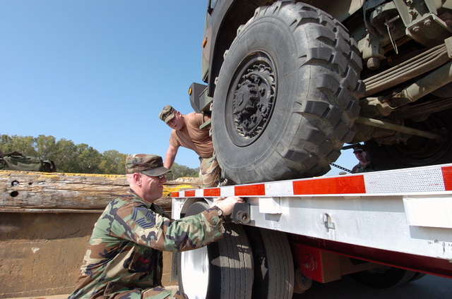 US Air Force (USAF) SENIOR MASTER Sergeant (SMSGT) Martin Leonard (foreground), 120th Fighter Wing (FW), Montana Air National Guard (MTANG), and USA Specialists (SPC) Jacob Kunz, 495th Transportation Battalion, Montana Army National Guard (MTARNG), work to remove the tie down chains from a USA Light Medium Tactical Vehicle (LMTV) being carried on a semi trailer after arrival at the Intermediate Staging Base (ISB), located in Alexandria, Louisiana (LA), during Hurricane Katrina relief efforts. (A3613)