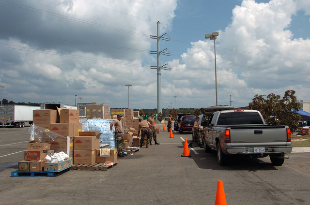 US Army (USA) Soldiers assigned to C Company, 1ST Battalion 111th Infantry, Pennsylvania Army National Guard (PAARNG) distribute relief supplies to residents at a vehicle Point Of Distribution (POD) in Covington, Louisiana (LA), during Hurricane Katrina relief efforts. (A3613)