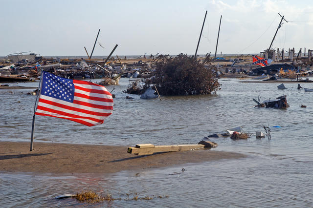 [Hurricane Rita] Holly Beach, La., October 3, 2005 - Two flags are planted in sand bars washed up and over the town that was once Holly Beach.  Very little along this stretch of Highway 27 that runs along the Gulf of Mexico was spared by Hurricane Rita.  Win Henderson / FEMA
