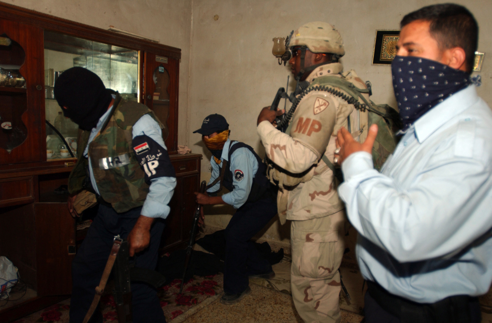 Iraqi police search a house during a joint cordon search