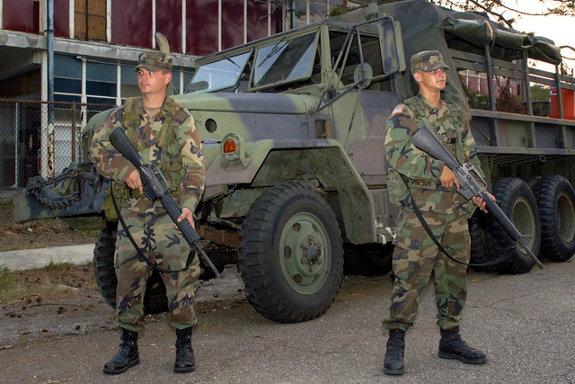 Armed with Colt 5.56 mm M16A2 Assault Rifles, SPECIALIST Fourth Class (SPC) Cliff Harden (left), of Shawnee and Private (PVT) Andrew Bean, of Agra, both from Battery B, 1ST Battalion, 160th Field Artillery, provide security outside of a Red Cross and Federal Emergency Management Agency (FEMA) relief point in New Orleans, Louisiana (LA), next to an M-923 5-ton Truck. (A3570)
