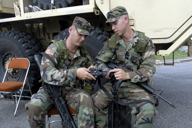 Oklahoma Army National Guard (OKARNG) Sergeant (SGT) Steven Schoeppach (right), shows SPECIALIST (SPC) Sean Cook how to attach a head band mount to a AN/PVS-4 Individual Weapon Night Sight scope during checkpoint operations in New Orleans, Louisiana (LA). SGT Schoeppach and SPC Cook, are both Artillerymen with Battery B, 1ST Battalion, 171st Field Artillery. OKARNG Soldiers are armed with a Colt 5.56 mm M16A2 Assault Rifles. (A3570)