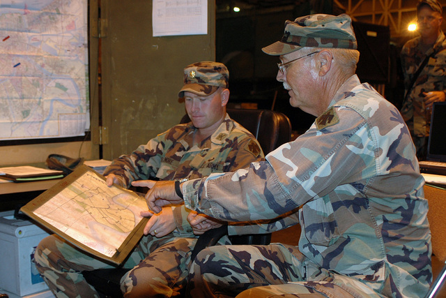 US Army (USA) Major (MAJ) Woody Elmore (background), listens as USA Sergeant First Class (SFC) Gary Wayland, updated him on the latest missions in his Area of Operations (AOR) in New Orleans, Louisiana (LA), during Hurricane Katrina relief operations. Both are members of 1ST Battalion, 160th Field Artillery, Oklahoma Army National Guard (OKARNG). (A3570)